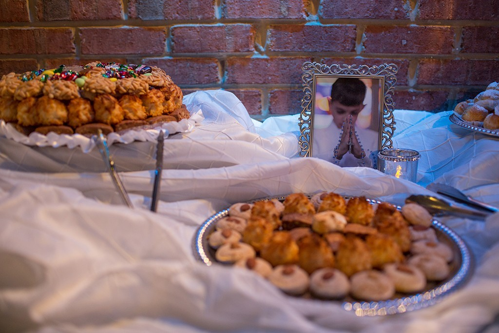 Table with two trays of cookies and a photo of a young boy at his confirmation