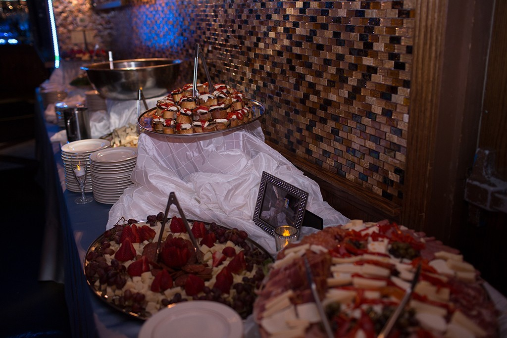 Catered table filled with trays of food and plates