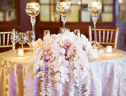 Table with wedding bouquet and wine glasses