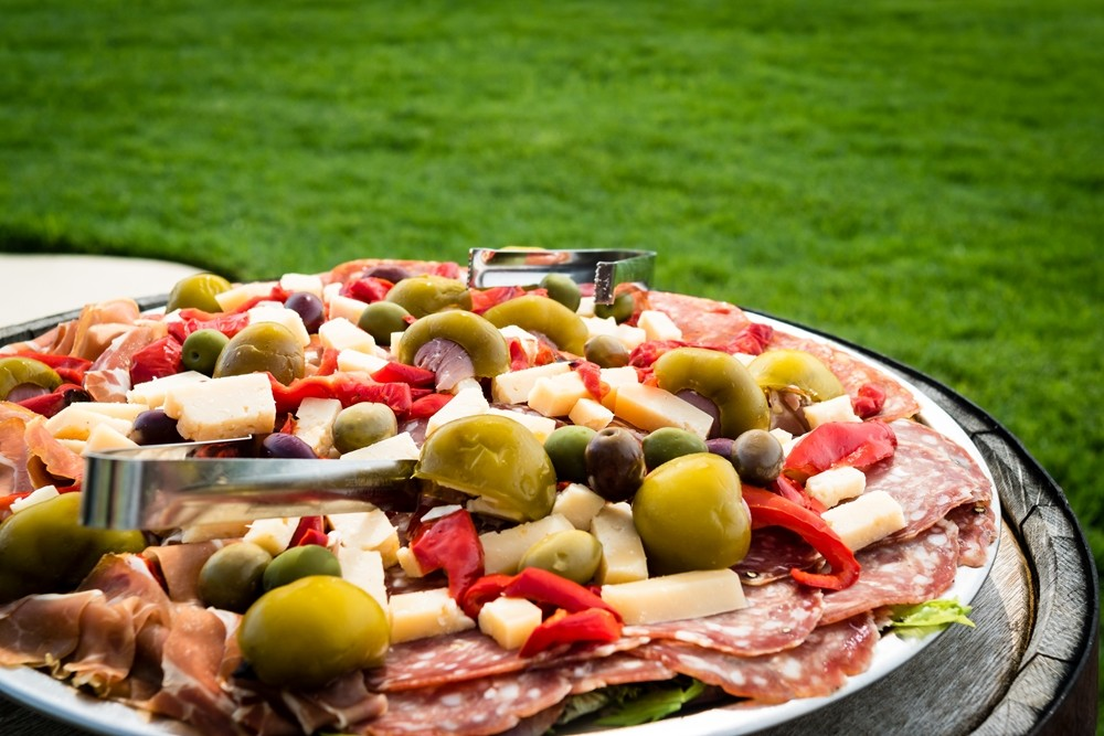 Tray with appetizers outdoors with green grass