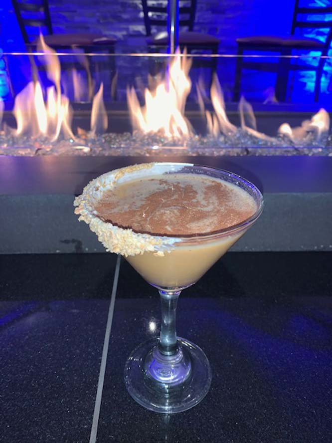 Cocktail in a martini glass with fireplace in background